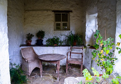A garden hideaway (rustyruth1959) Tags: nikon nikond3200 tamron16300mm uk wales northwales llynpeninsula plasynrhiw house manorhouse garden building walls window bush plant shrub chairs table woodenchairs woodentable furniture woodfurniture shelf potplants hidden whitewash whitepaint cane gardencane floor fern stone stonewalls glass windowframe rustic chairleg tableleg retreat sheltered wicker wickerchair paving leaves leaf stalk stem