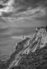 A ray of hope (Lloyd Austin) Tags: sigma nikon d5100 coastline coastal coast blackandwhite bnw bw mono monochrome hope rays arayofhope overcast light sunrays seascape atmospheric moody clouds sky landscape tide beach water ocean englishchannel sea lighthouse cliffs chalk england eastsussex eastbourne beachyhead
