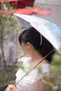 Young woman walking in city in hot summer, using umbrella to shade the sun