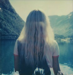 (mari-ann curtis) Tags: sx70 colour polaroid film rowboat morning sunshine portrait backlit mountains lake water blue turquoise oppstrynsvatnet hjelle norway roadtrip summer adventure friend laura light shadows reflections flare impossibleproject polaroidoriginals nostalgia memories rowing red peaceful fjord girl travel polaroidweek roidweek
