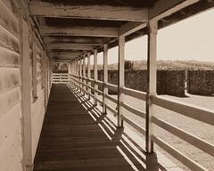 Ft Frederick SP ~ barracks porch view (karma (Karen)) Tags: bigpool maryland washingtonco forts fortfredericksp mdstateparks 1756 frenchindianwar mdhistory barracks porches fences railings stonewalls shadows sepia nrhp nhl sliderssunday hss topf25 cmwd