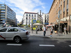 Places to go and people to meet (RubyGoes) Tags: madrid spain cafe trees sky windows buildings pavement traffic people yellow taxi