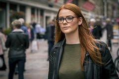 Ginger (Leanne Boulton) Tags: portrait people urban street candid portraiture streetphotography candidstreetphotography candidportrait streetportrait streetlife woman female girl pretty face facial expression eyes look emotion feeling mood glasses redhead ginger hair leather jacket style stylish fashion tone texture detail depthoffield bokeh splittone orangeteal naturallight outdoor light shade shadow orange teal city scene human life living humanity society culture canon canon5d 5dmkiii ef2470mmf28liiusm colour glasgow scotland uk