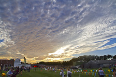 Waiting for the Finish (brucetopher) Tags: cloud sunset race running spectators men women boys girls crosscountry highschool sports sporting event colorful flags triangle clock observatory evening sky skies beauty crowd park field finishline finish timer racing run athletic