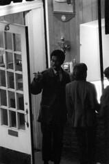 h77-68 07 (ndpa / s. lundeen, archivist) Tags: nick dewolf nickdewolf photographbynickdewolf blackwhite bw 1968 1960s 35mm october charlesstreet beaconhill candid people youngpeople boston massachusetts ma city citylife streetlife sliceoflife film monochrome blackandwhite fall autumn streetphotography night nighttime atnight nightlife sidewalk pedestrian storefront business window storewindow restaurant cafe subshop group man men youngman youngmen light shadows black africanamerican glasses eyeglasses door 45charlesstreet table condiments lamp opendoor evening afterdark finger point pointing