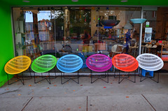 Choices (James_D_Images) Tags: store reflection white yellow magenta orange blue green leaves sidewalk street colourful chairs window storefront mainstreet vancouver britishcolumbia