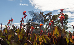 Bear sculpture, Kelowna (amanda & allan) Tags: kelowna britishcolumbia canada bear okanaganlake waterfrontpark stuartpark browerhatcher sculpture firstnation flowers orange cloud sky