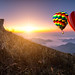 Hot air balloon with tourist is traveling into the peak of mountain and cloudscape at Phu chi fa in Chiangrai Provice, Thailand