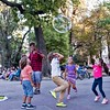 Fun with bubbles, Sofia (chrisjohnbeckett) Tags: square street urban people chidren jump jumping fun happiness happy joy reach bubble park entertainment sofia bulgaria chrisbeckett fujifilmx100f candid portrait candidgroup red floating above