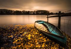 Autumn's AGM (Photography by Julia Martin) Tags: photographybyjuliamartin autumn autumnleaves fenceposts boat lake boatfullofleaves hss warm glow longexposure blueboat