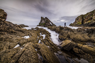 the precarious photographer at the famous Bow Fiddle Rock, Portknockie, Moray, Scotland, UK. Fine art long colour exposure
