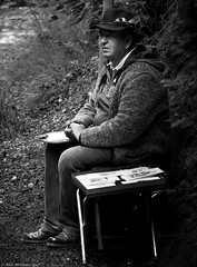 Artists and nature. (Neil. Moralee) Tags: neilmoralee neilmoraleenikond7200 man hat artist painter sketch germany sitting woodland forest traditional face portrait stool pictures selling sale nikon neil moralee d7200 black white mono monochrome shadow shade dapple light natural candid nature people sit tones shades leaf track sturdy shoes bush feather