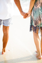Cropped View of Couple Holding Hands on Beach (Patricia W.) Tags: people couple male female woman man young adult middleaged casual sun dress shirt shorts sea sand sunny ocean beach asia holding hand walking standing relaxing content peaceful married wife husband boyfriend girlfriend friend love lover romance together vacation resort travelling summer tenderness outdoor cropped closeup vertical back view cut