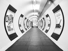 Distorted Life (Douguerreotype) Tags: london monochrome metro subway symmetry blackandwhite tube uk british underground urban mono city tunnel poster britain circle bw gb england