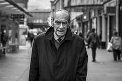 Marching On (Leanne Boulton) Tags: portrait people road urban street candid portraiture streetphotography candidstreetphotography candidportrait streetportrait eyecontact candideyecontact streetlife old elderly aged man male face facial expression eyes look emotion feeling mood atmosphere raincoat tone texture detail depthoffield bokeh naturallight outdoor light shade shadow city scene human life living humanity society culture canon canon5d 5dmkiii 70mm character ef2470mmf28liiusm black white blackwhite bw mono blackandwhite monochrome glasgow scotland uk