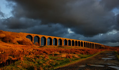 Radiance (images@twiston) Tags: radiance darkarches golden hour ribblehead viaduct ribbleheadviaduct sunlit arches settle carlisle settlecarlisle settleandcarlisle shadow shadows yorkshire northyorkshire midland railway main line 1875 battymoss battywifehole sebastopol belgravia jericho scheduledancientmonument radiantribblehead arch ribblesdale dales 3peaks yorkshire3peaks path track stone wall evening winter january national park yorkshiredalesnationalpark fields grass farm farmland moorland moor sunset dark clouds sky landscape 24 fells manmade stonework my365year sunshine ominous brooding broody puddle imagestwiston sundaylights