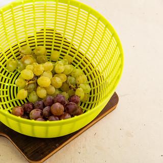 White and crimson grapes in a colander.