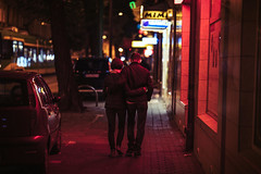 Upstage Center, Sidewalk Stories III (ewitsoe) Tags: sidewalk stories ewitsoe erikwitsoe city cityscape life love act canon sigma red glow lights bokeh couple arminarm home walking pedestrian jezyce poznan polska
