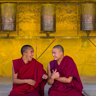 Monks debating in front of prayer wheels in a Rongwo monastery, Tongren County, Longwu, China
