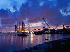 Twilight blues (elenaleong) Tags: westcoastpark sundown twilight industriallights cranes busyharbour elenaleong port cloudscape reflections machinery forklifts
