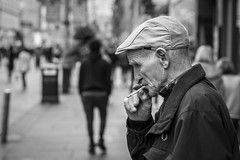 A Moment on the Lips (Leanne Boulton) Tags: people portrait urban street candid portraiture profile streetphotography candidstreetphotography candidportrait streetportrait streetlife old elderly man male face facial expression cap smoke smoker smoking cigarette inhaling skin wrinkles tone texture detail depthoffield bokeh naturallight outdoor light shade shadow city scene human life living humanity society culture canon canon5d 5dmkiii 70mm character ef2470mmf28liiusm black white blackwhite bw mono blackandwhite monochrome glasgow scotland uk