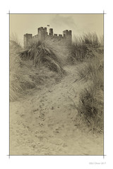 Sandcastle (Seven_Wishes) Tags: northumberland bamburgh aonb canoneos5dmark4 canonef24105mmf4lisii outdoor photoborder vintage mono monochrome sanddunes grasses beachgrass castle bamburghcastle sand beach