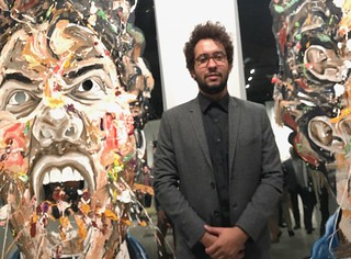 Artist William Osorio with his artwork at the grand opening of  LnS Gallery