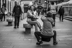 The Photographer and the Muse (Leanne Boulton) Tags: people monochrome urban street candid portrait streetphotography candidstreetphotography candidportrait streetlife woman women female face facial expression posture pose stance photographer crouching composition tone texture detail depthoffield bokeh selectivefocus naturallight outdoor light shade shadow city scene human life living humanity society culture tourism tourists canon canon5d 5dmkiii 70mm ef2470mmf28liiusm black white blackwhite bw mono blackandwhite glasgow scotland uk