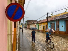 Rainy Day Cuba (street level) Tags: architecture caribbean streetphotography travel cobblestonestreet bicyclist umbrellas rain iphoneography cuba trinidad