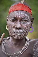 Mursi Warrior (Rod Waddington) Tags: africa african afrique afrika äthiopien ethiopia ethiopian ethnic etiopia ethnicity ethiopie etiopian omo omovalley outdoor omoriver portrait people painted face mursi tribe traditional tribal warrior feather stick donga beads