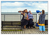 Sea breeze and close friends (Photos And All That) Tags: sea seas water waters lady ladies seaside windfarm windpower wind windy breeze breezy pier piers telescope telescopes portrait portraits group groupportrait fuji fujix100 fujixseries fujifilm x100 coast coastal bench benches scarf scarves pose posing poses friends dayout clouds sky cloud holiday holidays skegness skegnesspier smiles smiling