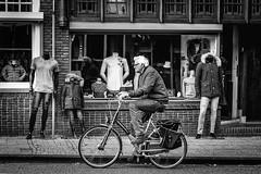 Man cycling in front of shop Zaandam Holland (James- Burke) Tags: bikes blackandwhite bw candid cycling cyclists dummys holland manequins monochrome netherlands shops zaandam shop road bike street windows