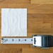 measuring sheet of toilet paper with measuring tape on wood table