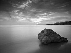 Alone Against Wind and Tide (Blueocean64) Tags: bw italy italia sicily sicilia agrigento siculiana siculianamarina tramonto coucherdesoleil sunset lapuestadelsol ciel sky cloudy clouds nuages mer mare mar sea rocks beach landscape paysage paisaje paesaggio longexposure extérieur light coastal outdoor seaside shore summer water nature natura seascape colline mont hill noiretblanc monochrome blackandwhite panasonic g5 美丽 艺术 摄影 日落 意大利 旅游 景观 天空 海