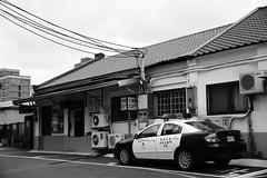 Cop Car at the Train Station (superzookeeper) Tags: formosa 5dmk4 5dmkiv canoneos5dmarkiv ef2470mmf28liiusm eos digital taiwan tw street copcar car bnw blackandwhite monochrome police policecar cop hsinchu hsinchustation