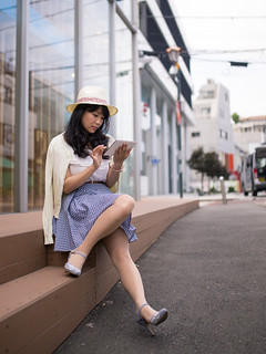 Young woman reading message on digital table in urban city
