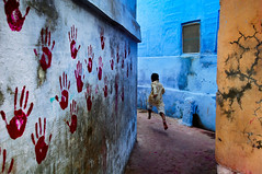 Boy in mid-flight (francesca.robbs) Tags: 2007 india jodhpur horizontal portrait streetscene outdoors outside exterior child kid young boy run running jump jumping action move moving movement midair midflight alley alleyway path wall walls paint painted hand hands print prints handprint handprints crack cracked cracks blue red yellow pbs2709 india10720 mcs2007002g070310720 nyc94317 iconicphotographs theunguardedmoment phaidon
