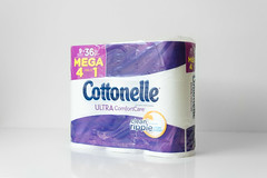 Package of Cottonelle toilet paper on white desk