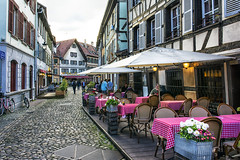 Dining in Strasbourg. (PLN54) Tags: cobblestone architecture dining tablecloths flowers sky