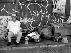 Meh... (gergelytakacs) Tags: man elderly old graffiti tag rubble water glasses cap birds wall tagging rug bag cart garbage meh indifferenceathens greece greek αθήνα athína