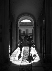 On the way home for dinner (PeterThoeny) Tags: varese italy palazzoestense palace hallway silhouette child people walk walking light shadow lightsandshadows town sunset blackandwhite monochrome 1xp raw nex6 photomatix selp1650 hdr qualityhdr qualityhdrphotography wall building corridor passage passageway cloister monestary santantonino fav200