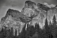 Bridalveil Fall with the Nearby Towering Peaks of Cathedral Rocks (Black & White, Yosemite National Park) (thor_mark ) Tags: nikond800e day5 triptopasoroblesandyosemite yosemitenationalpark lookingeast capturenx2edited colorefexpro silverefexpro2 blackwhite outside trees hillsideoftrees blueskieswithclouds nature landscape bridalveilfall waterfall 617ft188metres ahwahneecheenamepohono spiritofthepuffingwind mountains mountainsindistance mountainsoffindistance lowercathedralrock middlecathedralrock uppercathedralrock cathedralrocks pacificranges sierranevada yosemiterittersierranevada centralyosemitesierra yosemitevalley mountainside project365 portfolio california unitedstates