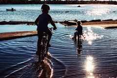 bike through the puddles (-liyen-) Tags: bicycles riding silhouettes children biking puddles lake sunlight earlyfall stillfun kids water lateafternoon fujix100f challengeyouwinner cyunanimous mpt580 matchpointwinner tournament cy2