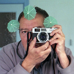 reflected self-portrait with Canonet 28 camera and green parasols (square crop) (pho-Tony) Tags: square cameraselfportraits canonet28 canonet 28 canon rangefinder compact automatic 35mm japan japanese f28 40mm 128 f40mm canoninc canonlens agfavista agfa vista iso 200 film poundland tetenal c41