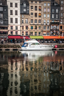 reflections of Quai Sainte Catherine split by a beautiful white launch - autumn at Honfleur, Calvados, Normandy, France