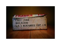 A gift from Pandora (CJS*64) Tags: inported inports inport box madeinchina tabletop cjs64 craigsunter nikon nikkorlens nikon1 nikonj5 whiteboarder whitebox fragile rubbish dumped art colour retro