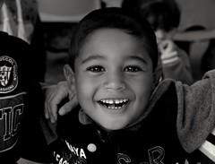Taken in Zaatari camp. A smile like that brings calmness to all the chaos. (DanaKhoudari) Tags: noiretblanc syrian refugee monochrome portrait smile blackandwhite human travel child happy canon 7dwf white light people bw boy