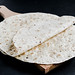 Tortilla wraps on wooden board on dark background