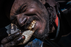 HIGH calories (Axel Halbgebauer) Tags: street streetphotography sony sonyalpha sonya9 closeup face fe portrait people india eating teeth hands dirty