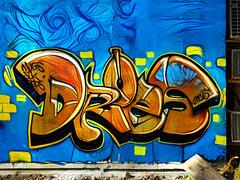 Dr Oes (Steve Taylor (Photography)) Tags: mugs slk rods droes 2016 art graffiti mural streetart tag blue black gold brown concrete wood newzealand nz southisland canterbury christchurch cbd city heatpump acu plank digital yellow texture
